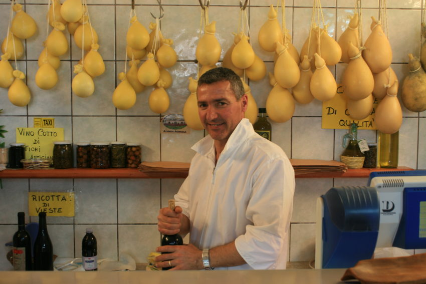 Cheese vendor Costanzo Laprocina with a backdrop of caciocavallo cheese in his shop in Vieste, Puglia