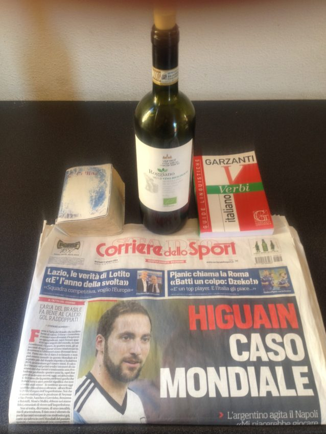 The essential tools of learning Italian: an Italian dictionary (notice how well worn), an Italian verb book, an Italian newspaper and the first of many bottles of Italian wine.