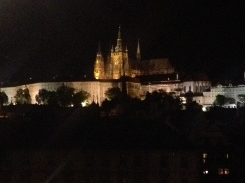 Prague Castle dominates the city skyline at night.