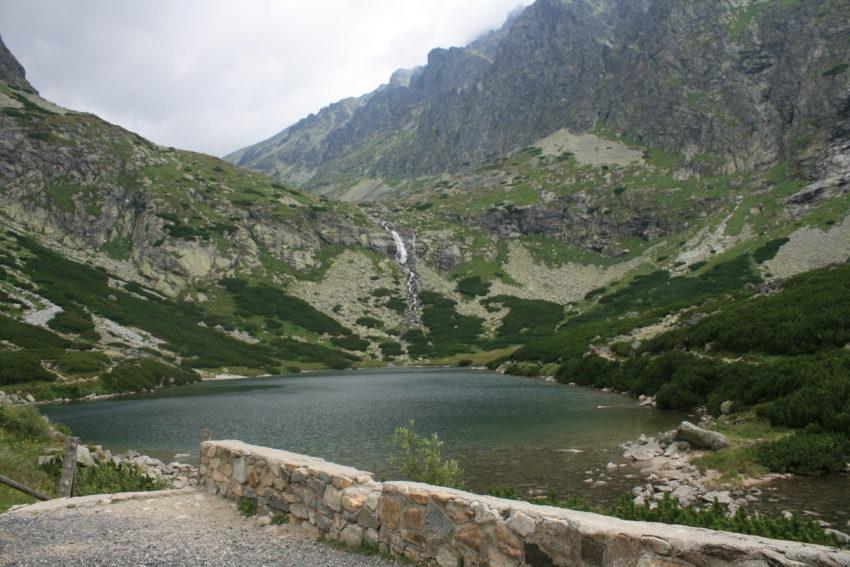Water cascades down a mountain into a lake.