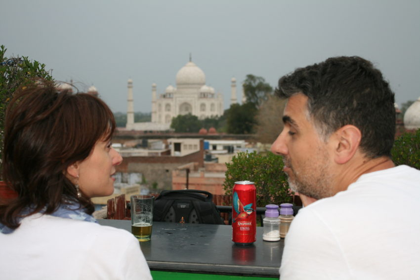A couple enjoy a view of the Taj from the rooftop restaurant at the Saniya Palace Hotel.