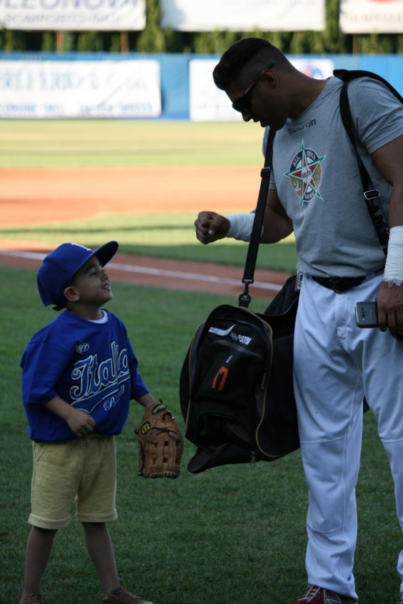 A young fan gets a fist bump from a member of the Italian Baseball League All-Star Team.