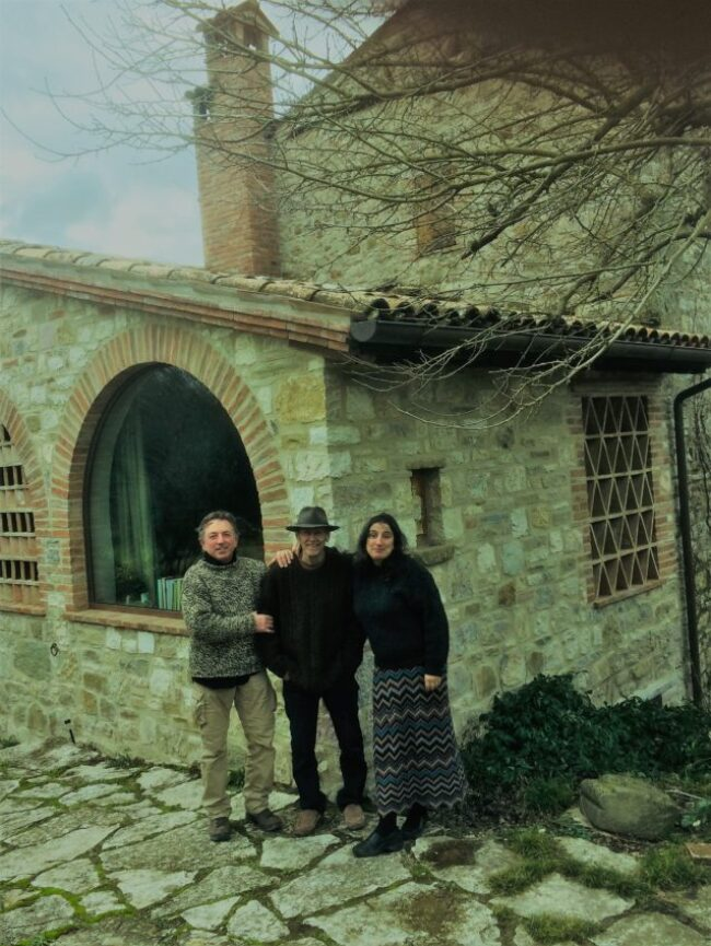 Fabrizio Bizzarri, Ev Thomas and Claudia Rizza stand in front of Thomas' and Rizza's 800-year-old house in Umbria.