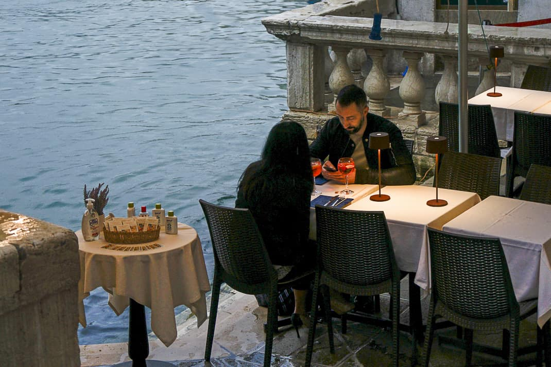 A lone couple have a drink below the usually bustling Rialto Bridge.