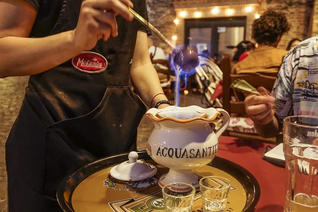 A waitress lights the fire on the Acquasanta, the local orange-flavored liqueur.